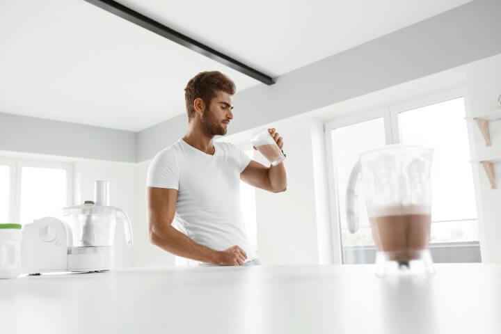 Man on white shirt drink his protein shake in the morning